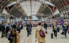 Travelers walk through a crowded Paddington Station in London