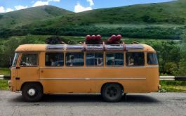 Passengers sit in an old yellow bus that idles on the side of the road with green mountains and blue sky in the background