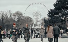 Armed military personnel and tourists walk along the CHamps-Elysees during Carnival. A ferris wheel is seen in the background.