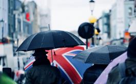 People walking on a crowded London street in the rain, holding umbrellas