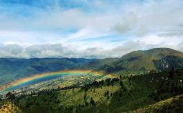 A rainbow appears over green hills in Ecuador